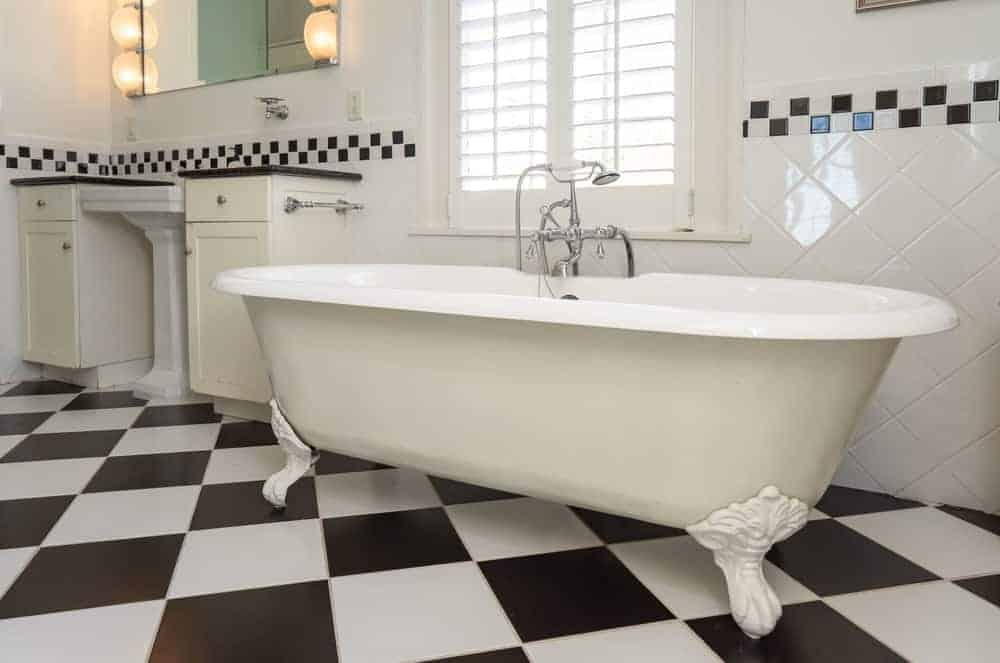 The white freestanding bathtub is placed under a window with white shutters to bring in natural lighting.