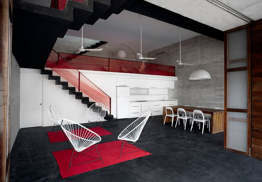 This simple and minimalist living room has four thin single chairs that are complemented by the dynamic red area rugs that stand out against the black floor and ceiling.