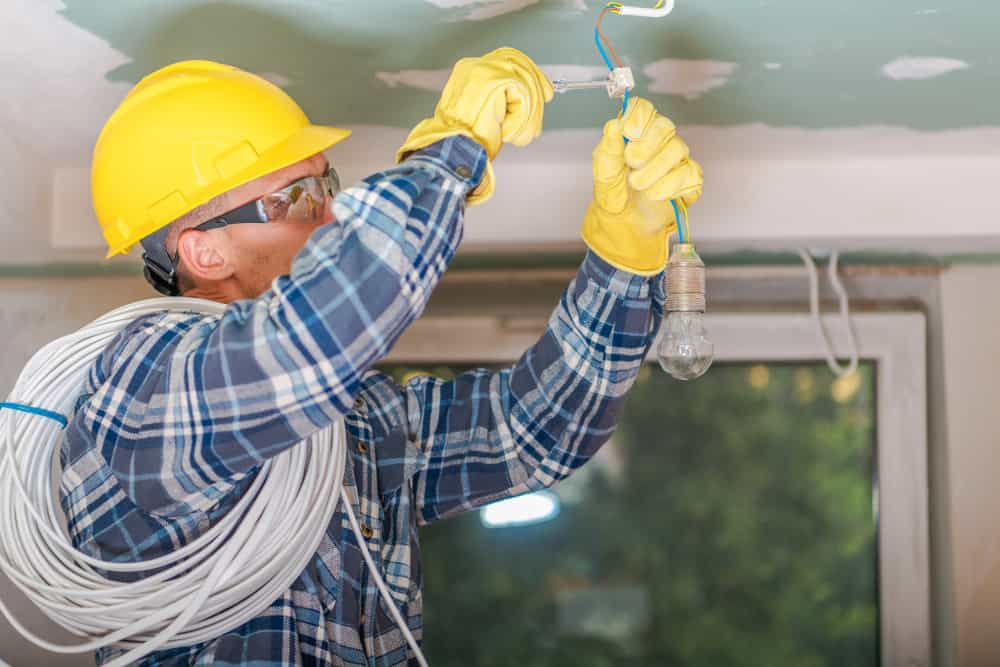 Electrician wiring a ceiling