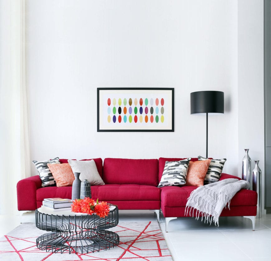 The bright and white walls of this living room is complemented by the vibrant red L-shaped sectional sofa along with various black accents like the coffee table, standing lamp and the patterned pillows of the sofa.