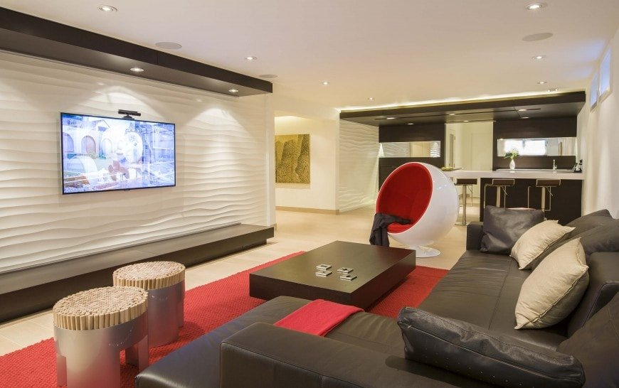 The fantastic living room has bright white walls and ceiling. These are contrasted by the vibrant red area rug that matches with the modern egg chair as well as the large black L-shaped sectional sofa that pairs with the coffee table.