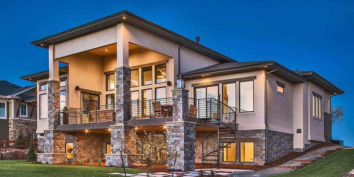 A modern home that boasts of charming stone wall accents on the base to pair with its greige exterior walls and warm yellow outdoor lights.