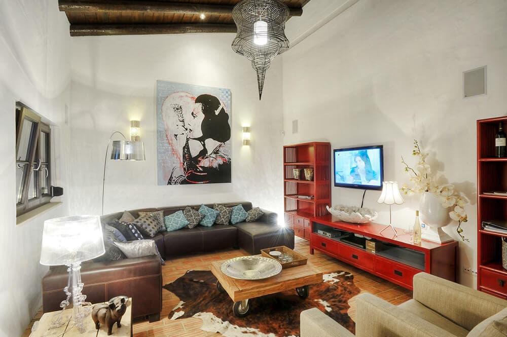 This gorgeous living room has white walls and a wooden shed ceiling that makes the black leather sofa set stand out as well as the vibrant red entertainment cabinet and shelves by the TV.