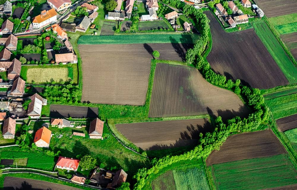 Aerial view of the countryside with village and fields of crops.