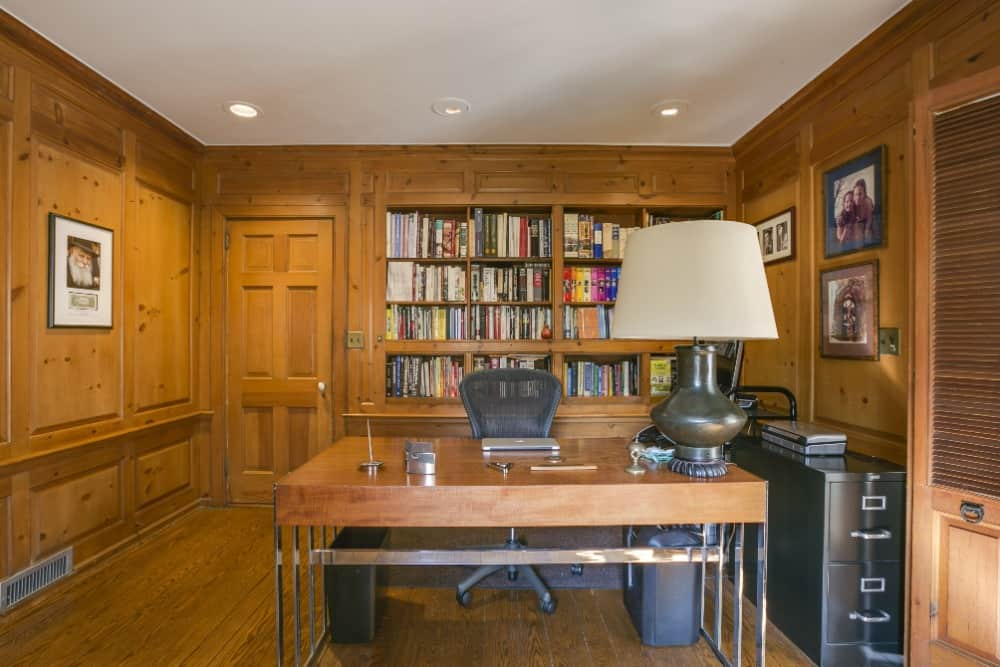 This home office features brown walls matching the hardwood flooring. The room has a stylish table and chair set along with built-in bookshelves at the back. Images courtesy of Toptenrealestatedeals.com.
