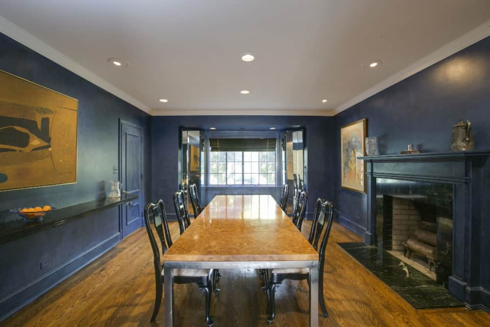 Large formal living room boasting a rectangular dining table set along with a fireplace on the side, surrounded by navy blue walls. Images courtesy of Toptenrealestatedeals.com.