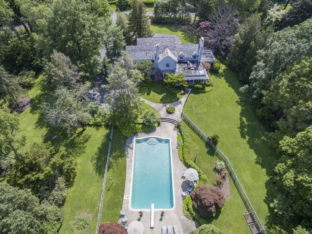 Bird's eye view of the property boasting its large swimming pool and house's exterior surrounded by the lush landscape. Images courtesy of Toptenrealestatedeals.com.