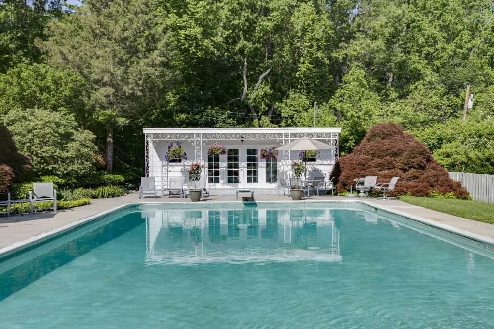 The swimming pool of the house, set in the backyard is surrounded by the lush landscape. Images courtesy of Toptenrealestatedeals.com.