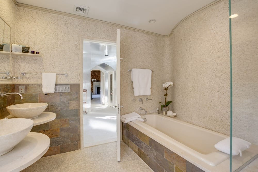 A bathroom with two stylish sinks and a drop-in soaking tub, along with a walk-in shower room. Images courtesy of Toptenrealestatedeals.com.