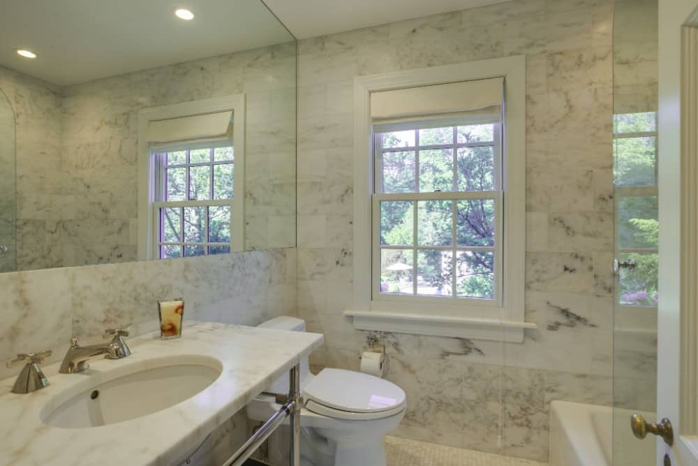 This bathroom boasts gorgeous marble tiles walls. It also has a charming sink counter and a walk-in shower room. Images courtesy of Toptenrealestatedeals.com.