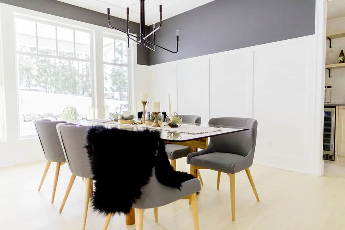 Light and airy dining room with gray wingback chairs and a glass top dining table illuminated by an industrial chandelier. The room showcases white wainscoting under gray walls and framed windows that let plenty of natural light in.
