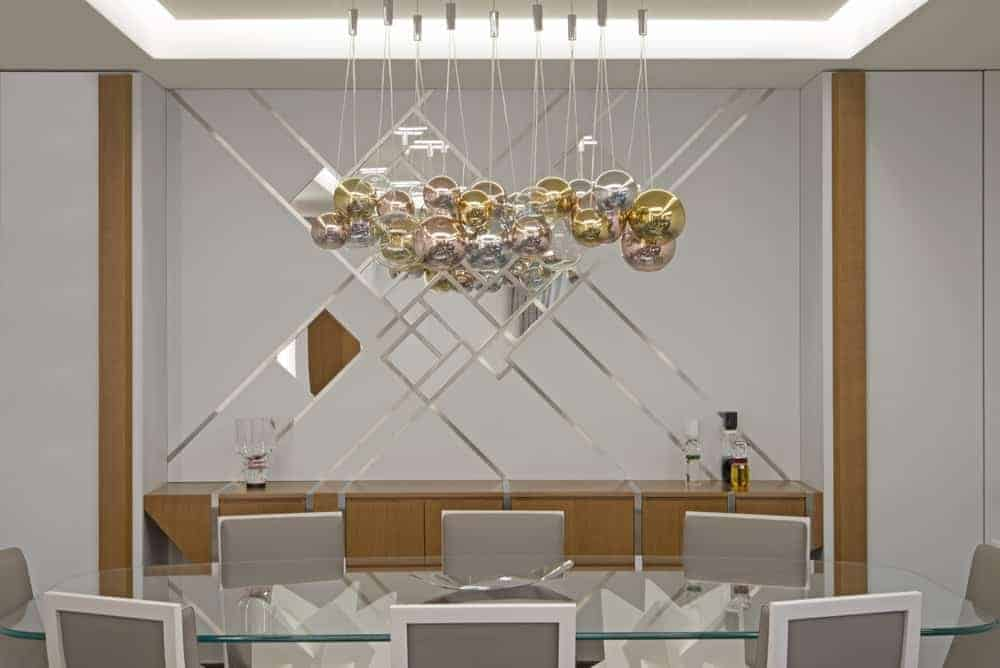 Striking silver strips with mirrors above the wooden console table along with cluster chandelier provide a luxurious feel in this dining room. It has a glass top dining table and sleek gray chairs situated underneath the glowing tray ceiling.