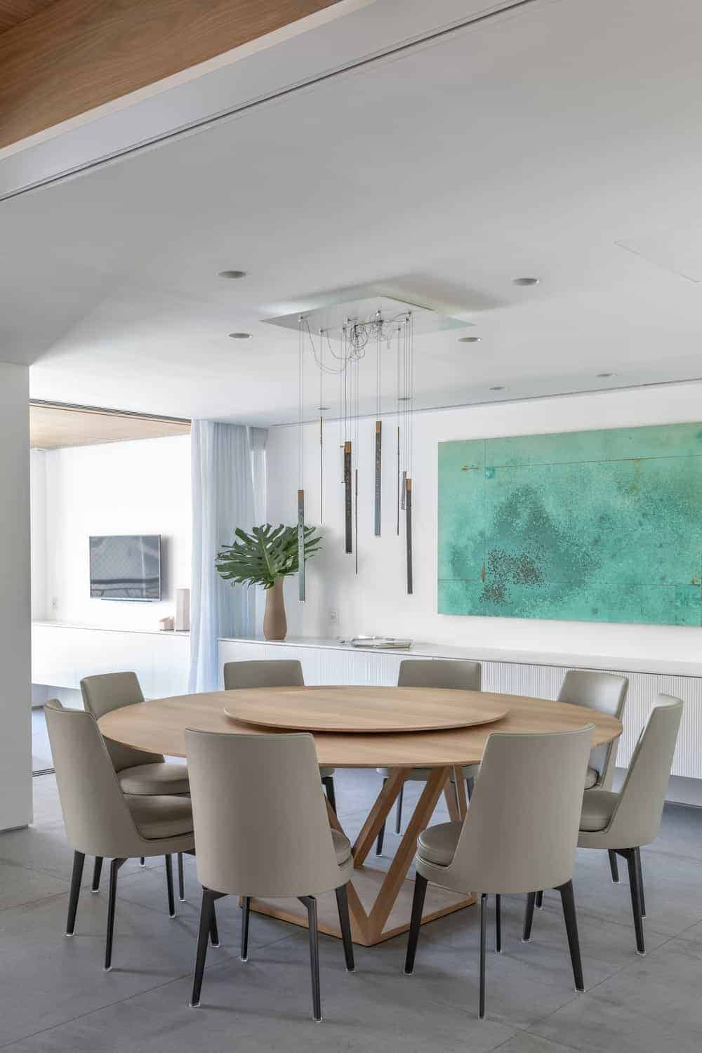 A fresh dining area decorated with an abstract painting, a lovely vase and sleek pendants hanging over the round dining table. It has concrete tiled flooring and a regular white ceiling fitted with recessed lights.