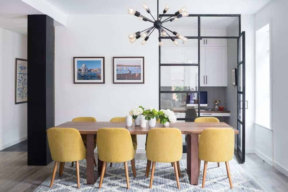 Yellow contemporary chairs add a pop of color in this white dining room. It features a sputnik chandelier and a pair of framed wall arts resting next to the glazed door.