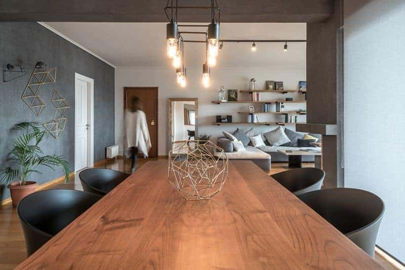 A warm dining space with black round back chairs and a wooden dining table that matches the hardwood flooring. Industrial bulbs along with geometric decor add character in the area.