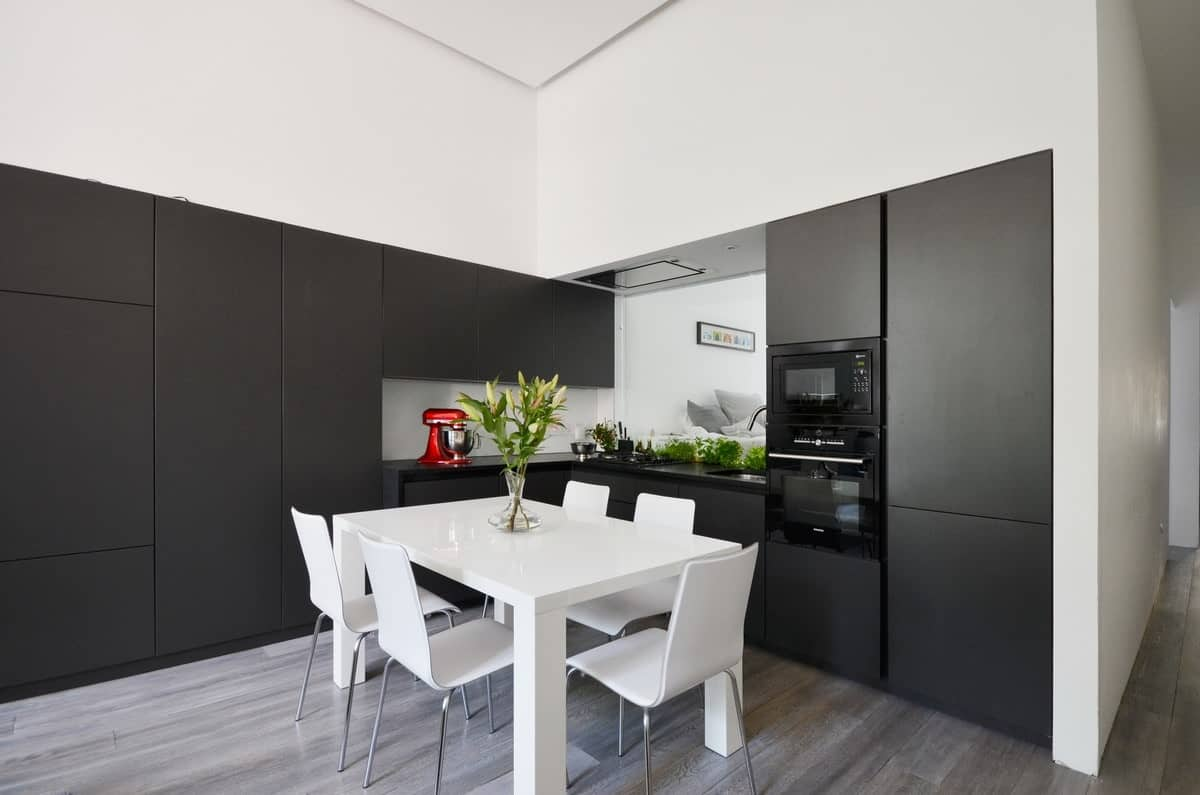 Built-in black cabinets provide a sleek contrast against the modern white dining set and pristine walls. Green plants, on the other hand, liven the space and create a refreshing ambiance.