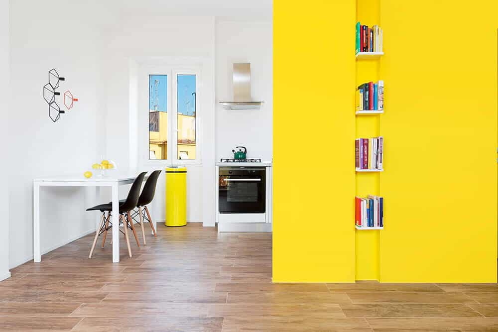 A spacious area with dining space on the side featuring black modern chairs and a white dining table that blends in with the walls. Vibrant yellow tones enliven the room.