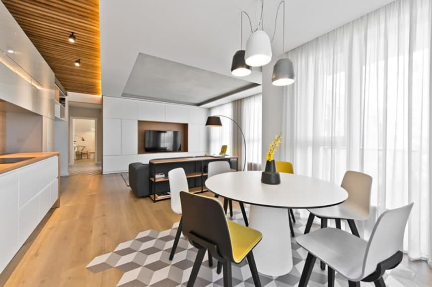 Modern dining space showcasing a round dining table and contemporary chairs defined by an interesting geometric decal on the hardwood flooring. It is lit by dome pendants along with natural light from the full height windows covered in sheer curtains.