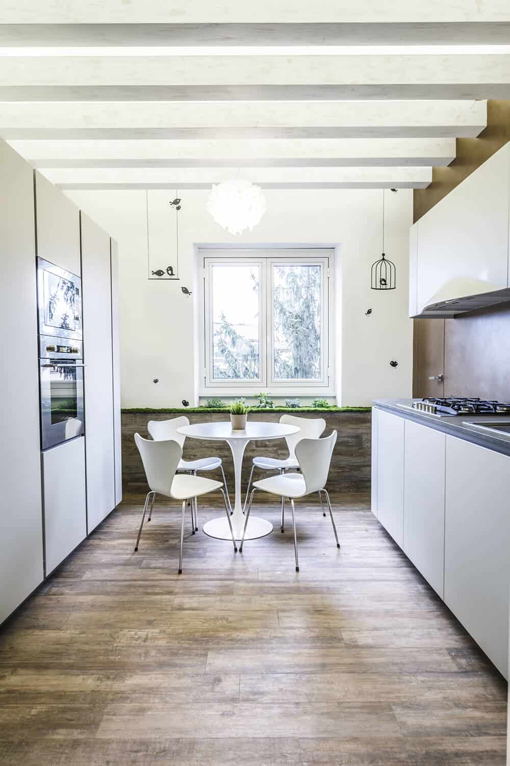 Sleek exposed beams along the ceiling add a nice textural contrast to the sleek surfaces of the cabinetry and countertops. White wingback chairs paired with a round dining table stand out against the wide plank flooring and lower wooden wall.
