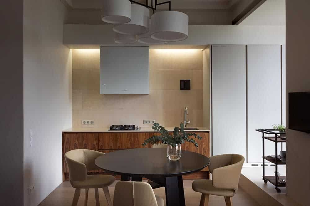 Beige chairs paired with a round dining table blends well with the light hardwood flooring. It is complemented by a cluster of drum pendants hanging from the tray ceiling.