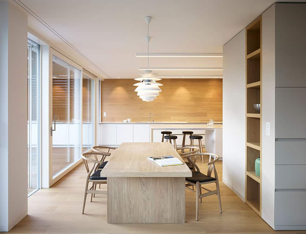 A cozy dining area boasting an all wood dining table that perfectly matches the hardwood flooring. It is surrounded by cushioned round back chairs and stylish white pendants that illuminate the area.
