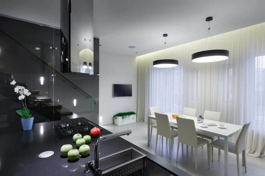 The dining table and chairs are monochromatic and correspond charmingly with the ongoing color scheme throughout the house. A waterfall of sheer white curtains covers the windows that line the wall.