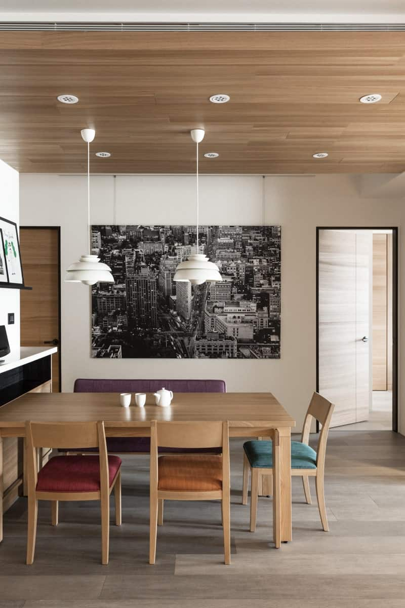 The dining table is surrounded by matching wood chairs with accent cushions in purple, red, orange, and blue for a burst of color amidst the neutral-toned space. This area also holds a hardwood ceiling.