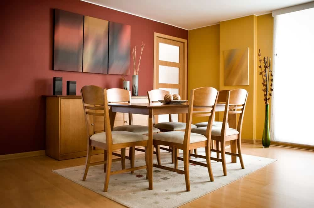 Apartment dining room with wooden buffet table, a matching dining set over a beige rug, hardwood flooring and multi-colored walls adorned by abstract paintings.
