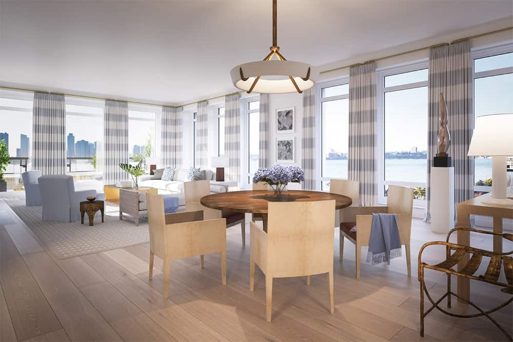 Light and airy dining area with wooden chairs that blends in with the wide plank flooring along with a round dining table illuminated by a stylish pendant. The room is surrounded by floor to ceiling windows overlooking the mesmerizing river.