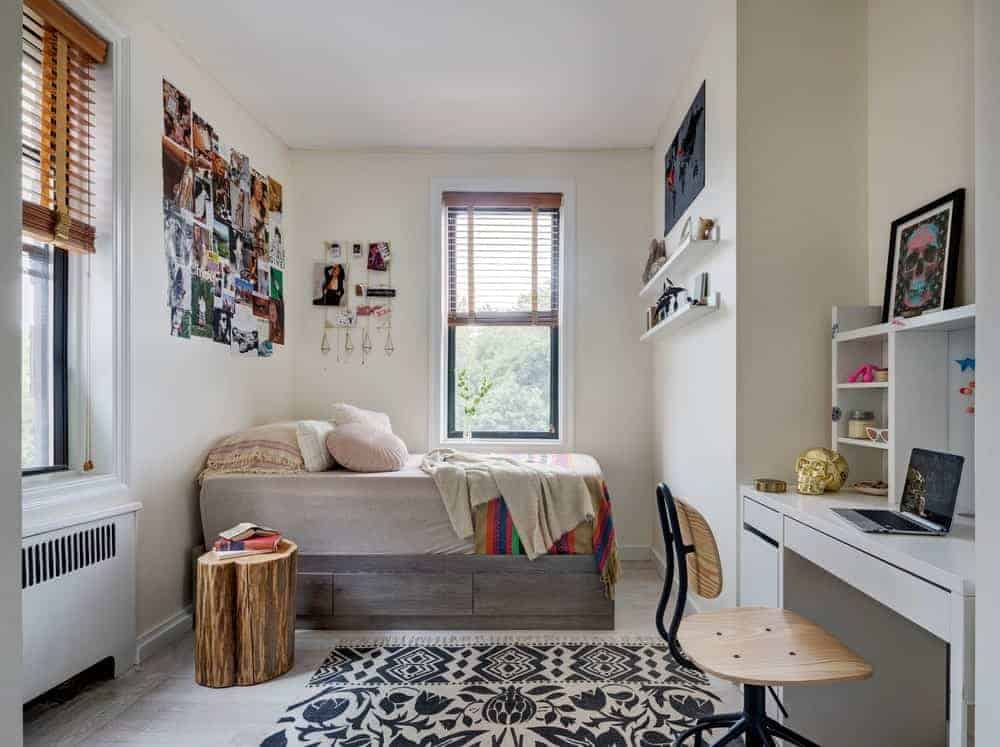 A home office integrated into the bedroom showcasing a sleek white desk topped with shelvings. It is paired with a wooden chair that sits on a black floral rug.