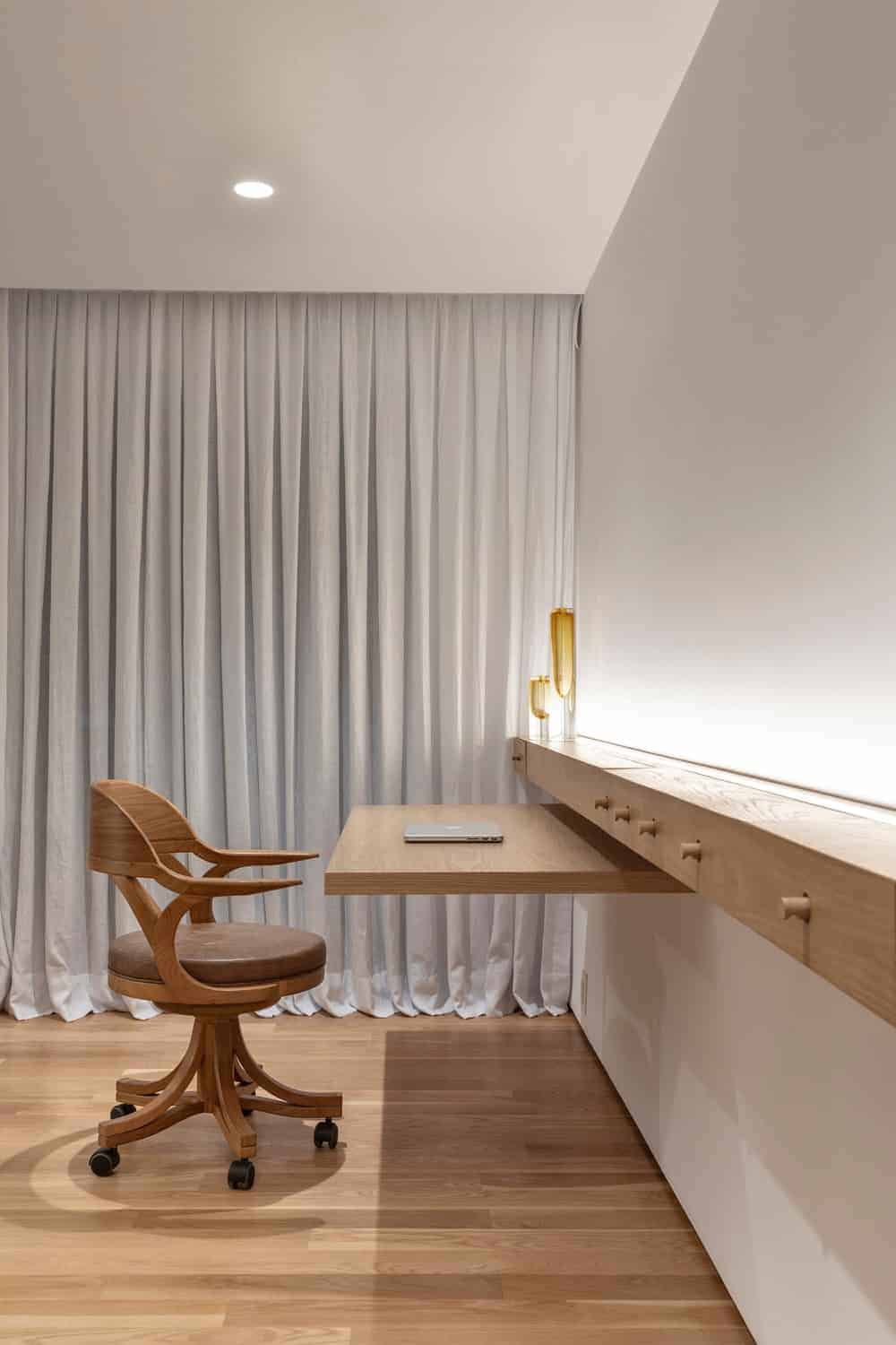 A cozy home office with a round back swivel chair and a built-in desk that matches the hardwood flooring. White drapes along with ambient lighting create warmth in the room.