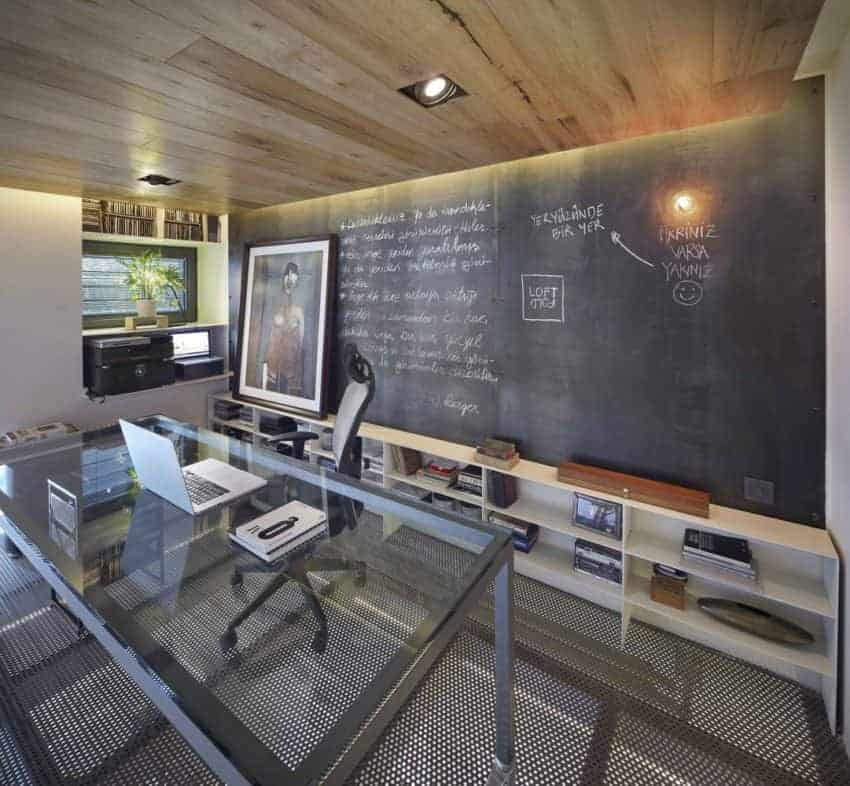 An industrial home office is designed with perforated flooring and a wood-paneled ceiling fitted with recessed lights. It is filled with a glass top desk paired with a leather swivel chair along with built-in shelving situated against the chalkboard wall.