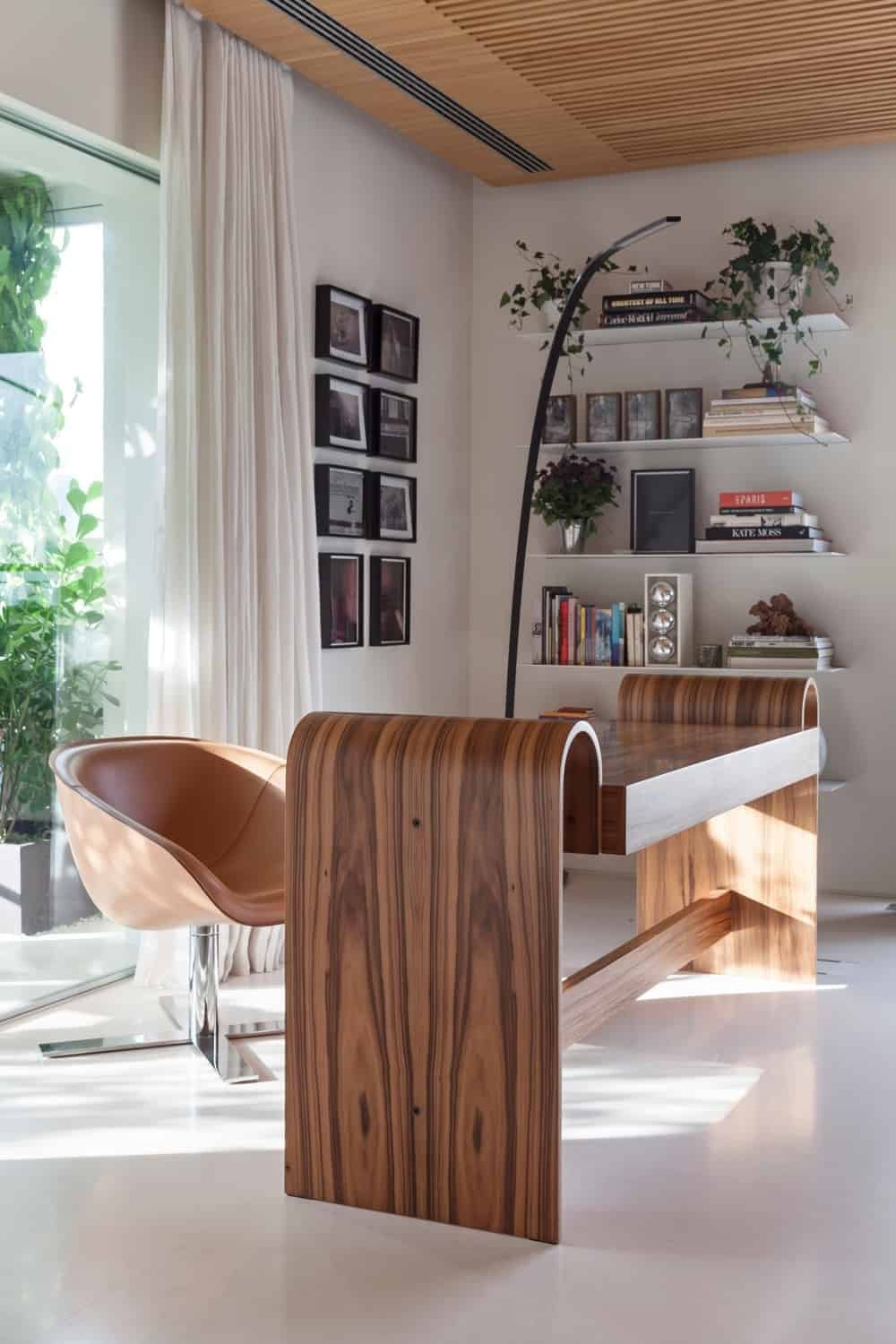 A serene home office with white flooring and walls adorned by gallery frames. It boasts a stylish wooden desk that complements the round back chair along with floating shelves filled with books and potted plants.