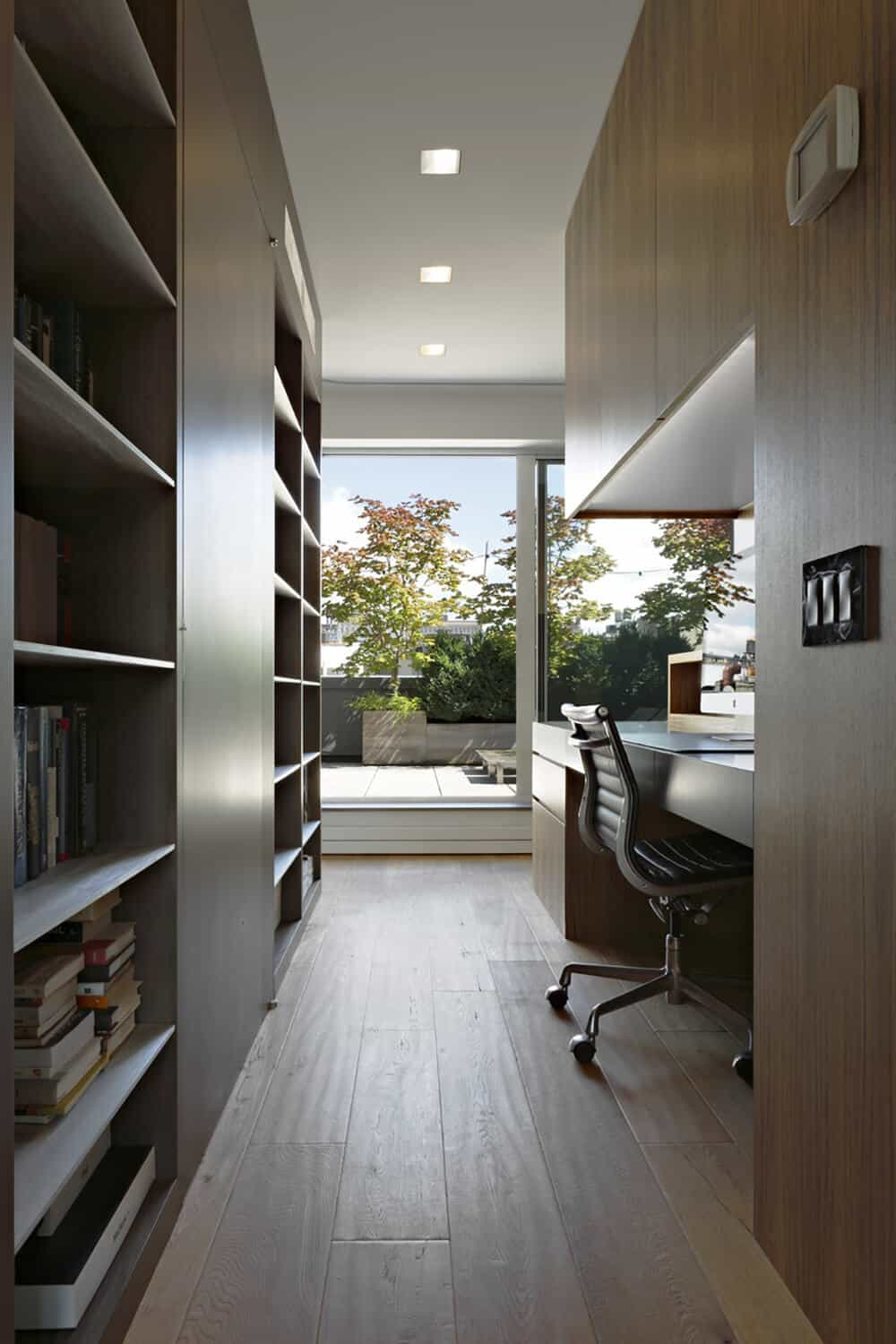 Natural wooden elements run throughout this home office that is well lit by the massive sliding door leading out to the terrace. It has a built-in bookcase and desk that is complemented by a black swivel chair.