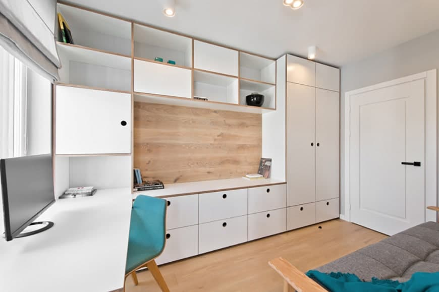 The home office is awash in storage and shelving options with cabinetry and open cupboards covering an entire wall. The built-in desk meets a countertop and natural wood backsplash while a singular blue chair and blanket offer a small burst of color.