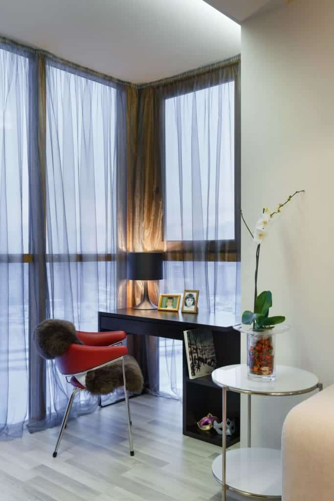A corner home office with light hardwood flooring and full height glazing covered in sheer curtains. It is furnished with a luxury fur chair and a black desk topped by a sleek table lamp.