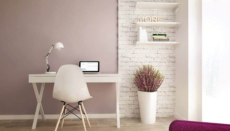 This spare, minimalist home office centers on a white writing desk in a simple X-frame, with a rustic white brick wall adding texture in the corner. Built-in shelving adorns the corner while another appearance of light pink informs the wall.