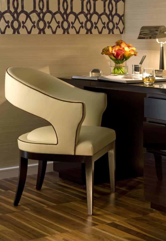 A corner office space with a rich dark wood desk and a stylish round back chair that creates an elegant accent.