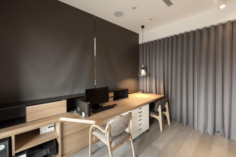 This home office is made private by the dividing curtains and dark grey shades pull down over the lengthy wooden desk. Ambient lighting from the dome pendant creates a cozy feel in the room.