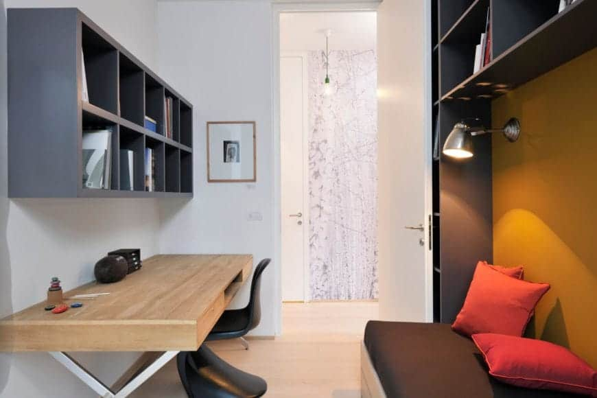 This cozy office includes mounted upper shelving in dark tones, reflecting the exterior panels with a daybed on the right and natural wood desk on left. The birch tree wallpaper can be seen in the hall.