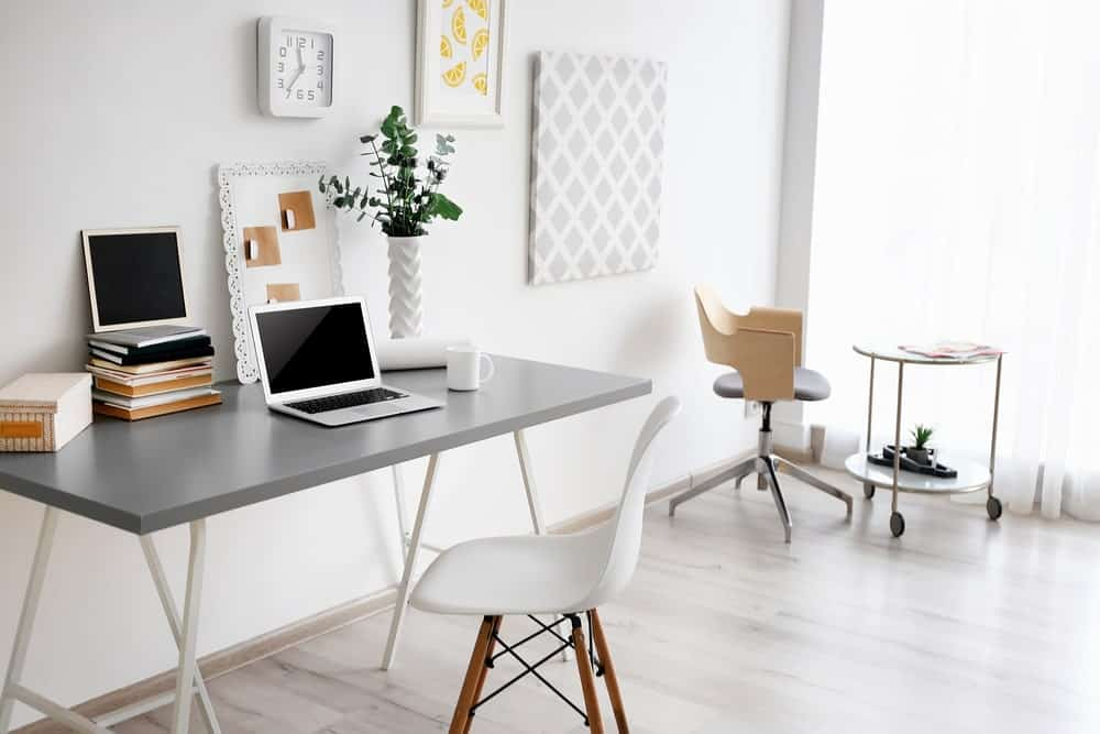 Apartment home office with light hardwood flooring, white walls, patterned artworks, a gray desk paired with a modern chair and a sitting area on the side.