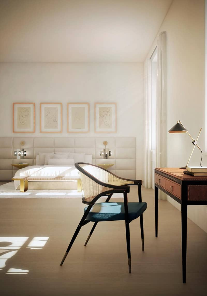 An office space inside the primary bedroom showcasing a gorgeous wooden desk paired with a sleek cushioned chair. White walls and ceiling along with a hardwood flooring fill the room.