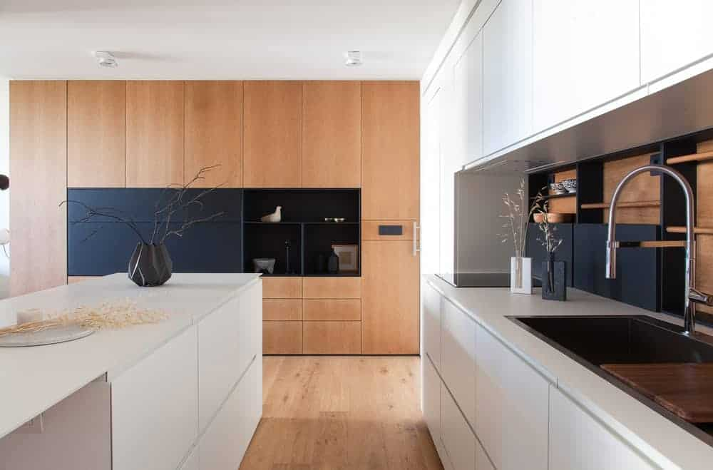 This kitchen has a modern design showcasing full height cabinetry in a wood finish with black shelving in the middle and a white island that matches the facing cabinets and counter.