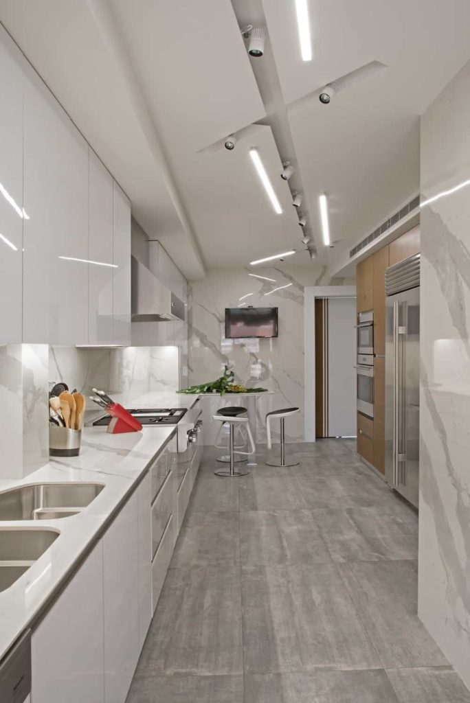 A galley kitchen with white glossy cabinets and marble countertop that extends to the walls and backsplash. It boasts stainless steel appliances and a sitting area facing the wall-mounted TV.
