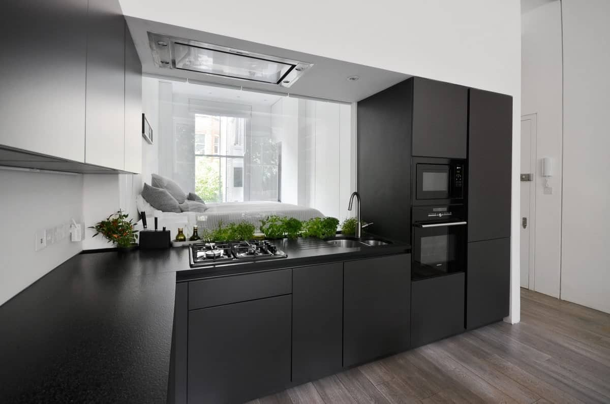 Sleek kitchen with contrasting white and charcoal cabinets fitted with black appliances. It features a mirrored backsplash where the bedroom is being reflected.