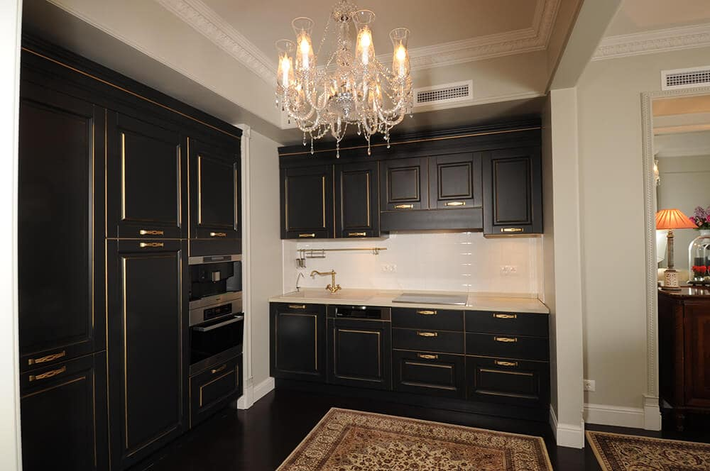 An elegant kitchen illuminated by a beaded chandelier that hung over a classic rug. It features matte black cabinetry accented with gold hardware and trims.