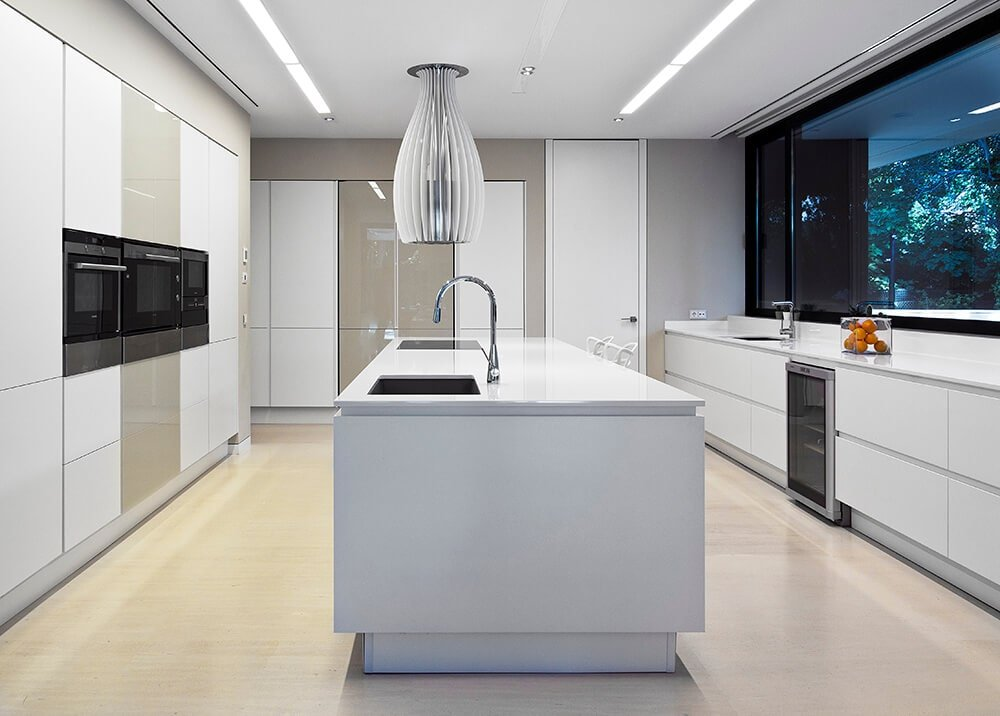 A stylish vent hood is suspended over the white island bar fitted with built-in cooktop and an undermount sink. Minimalist cabinetry and counter completed the clean look.