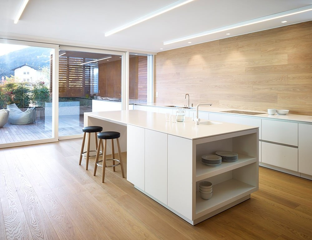 Airy kitchen with pristine white cabinets and a matching island bar complemented by round stools. The room has full-height glazing and a hardwood flooring that extends to the paneled backsplash.
