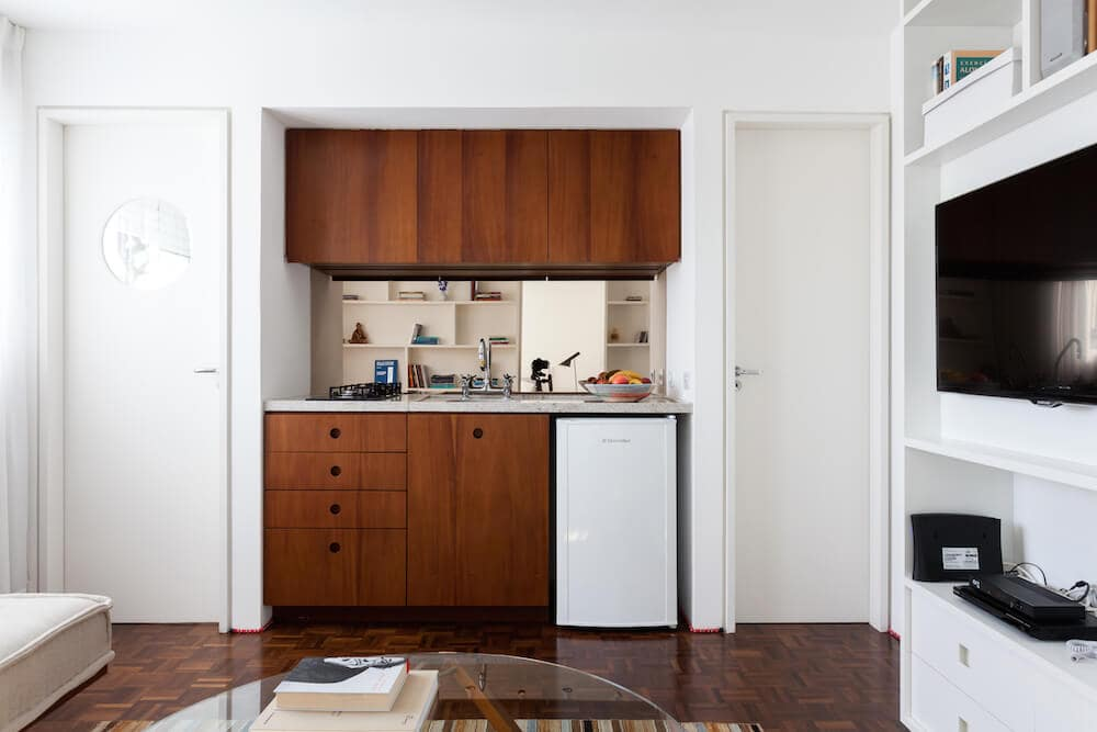 Identical white doors flanked the small kitchen that's composed of rich wood cabinetry and a granite countertop. It includes a small white fridge and a sink fitted with chrome fixtures.