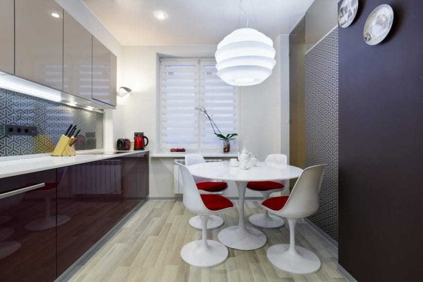 An eat-in kitchen designed with decorative plates and a patterned backsplash that matches the opposite wall. It is filled with high gloss cabinets and modern round dining set lighted by an oversized glass pendant.